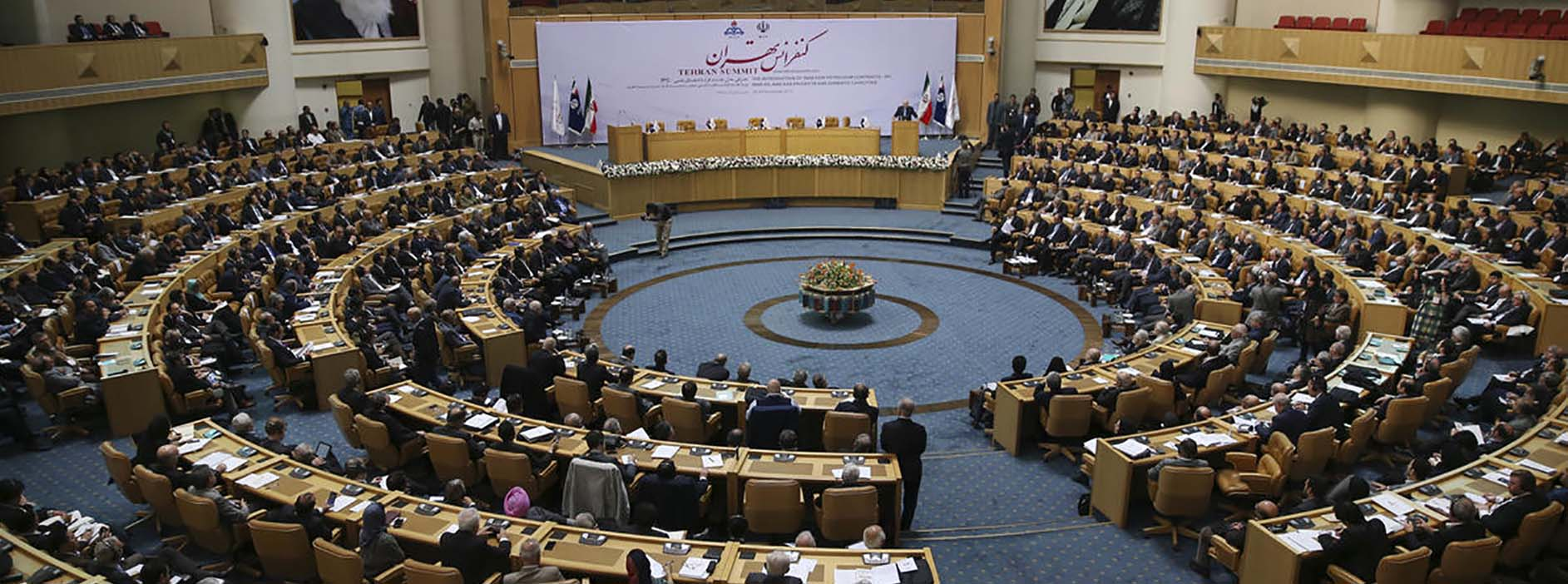 Participants listen to a speaker during Iran Petroleum Contracts Conference in Tehran, Iran, Saturday, Nov. 28, 2015. Iran has unveiled a new model of oil contracts aimed at attracting foreign investment once sanctions are lifted under a landmark nuclear deal reached earlier this year. Portraits of the late Iranian revolutionary founder Ayatollah Khomeini, left, and Supreme leader Ayatollah Ali Khamenei hang on the wall. (AP Photo/Vahid Salemi)